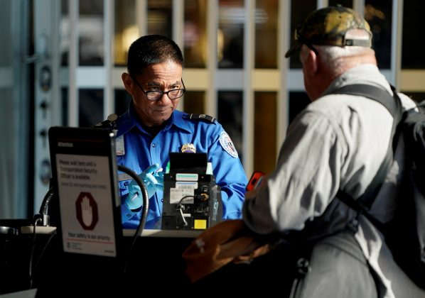An employee with the Transportation Security Administration (TSA) checks the documents of a traveler at Reagan National Airport in Washington, U.S., January 6, 2019. REUTERS/Joshua Roberts/File Photo