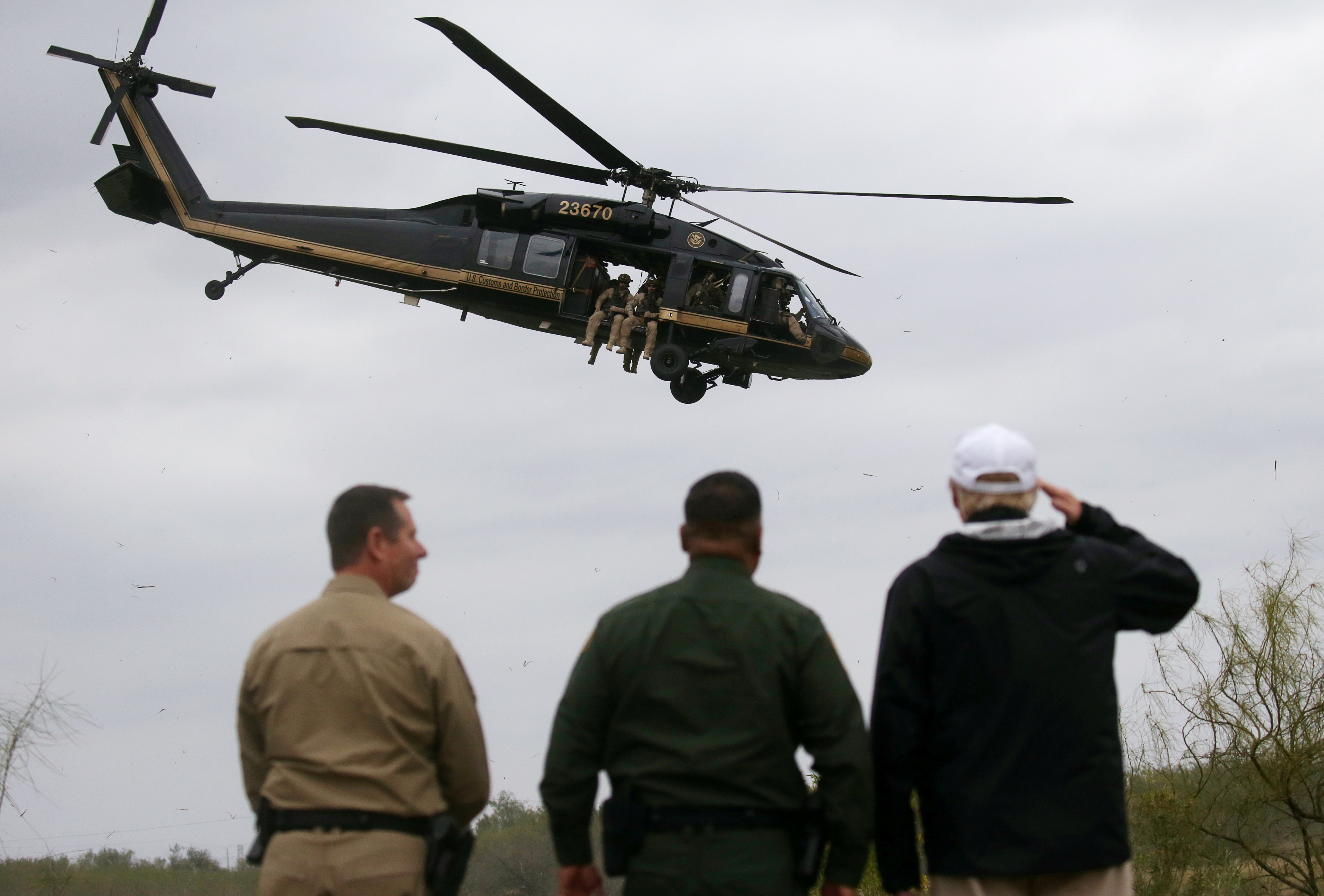 President Donald Trump salutes a U.S. Border Patrol helicopter as he stands with U.S. Border Patrol agents as it flies over the Rio Grande River during his visit to the U.S. - Mexico border in Mission, Texas, U.S., January 10, 2019. REUTERS/Leah Millis