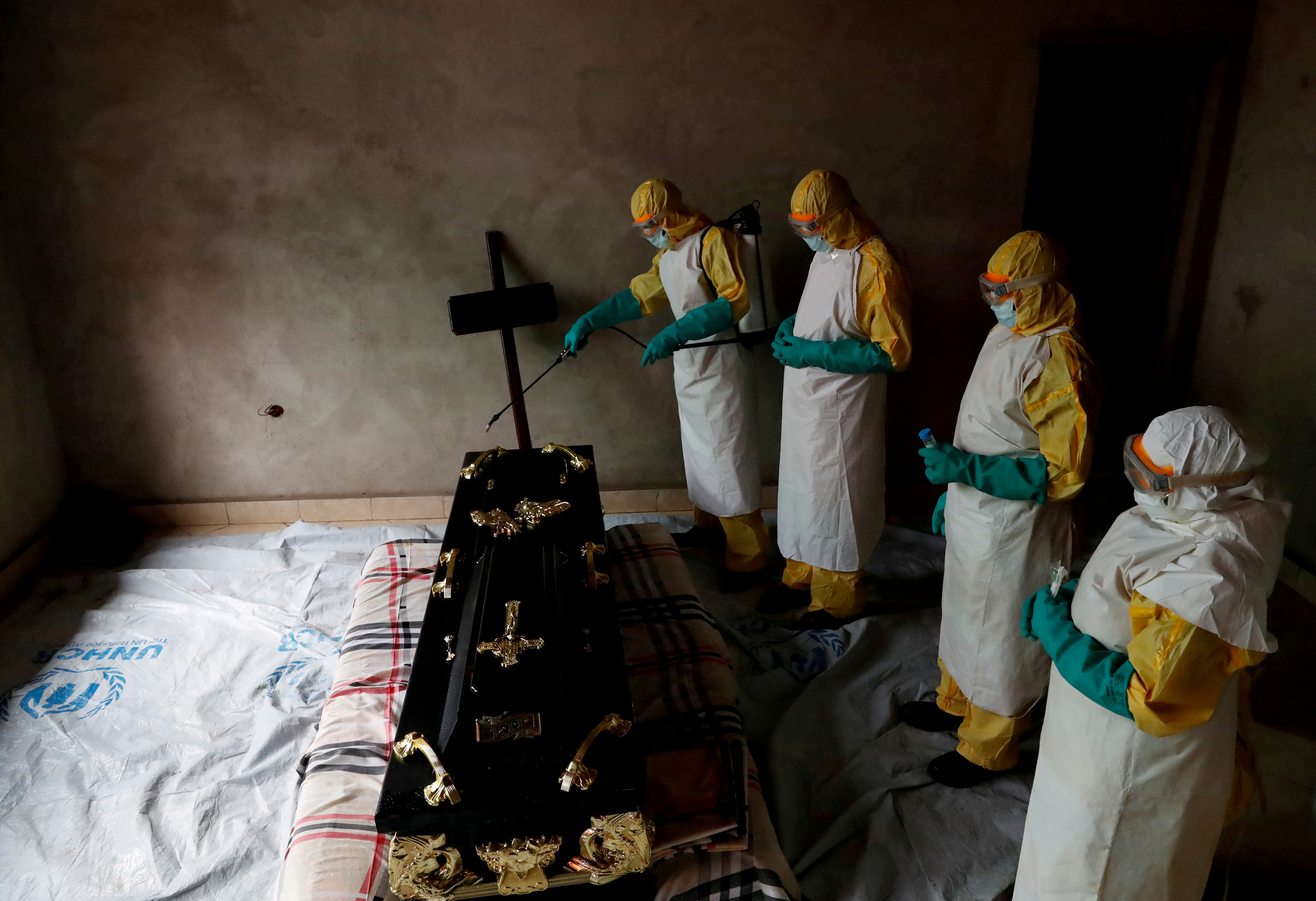 FILE PHOTO: A healthcare worker sprays a room during a funeral of a person who is suspected of dying of Ebola in Beni, North Kivu Province of Democratic Republic of Congo, December 9, 2018. REUTERS/Goran Tomasevic/File Photo