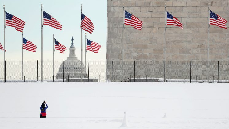 FILE PHOTO: Following a weekend snowstorm, the dome of the U.S. Capitol is seen in the distance as a jogger stops to photograph the Washington Monument in Washington U.S., January 14, 2019. REUTERS/Kevin Lamarque