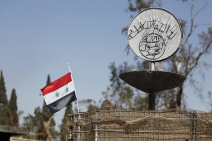 FILE PHOTO: A Syrian national flag flutters next to the Islamic State's slogan at a roundabout where executions were carried out by ISIS militants in the city of Palmyra, in Homs Governorate, Syria in this April 1, 2016 file photo. Omar Sanadiki/Files/File Photo