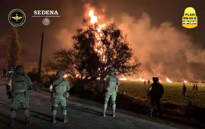Military personnel watch as flames engulf an area after a ruptured fuel pipeline exploded, in the municipality of Tlahuelilpan, Hidalgo, Mexico, near the Tula refinery of state oil firm Petroleos Mexicanos (Pemex), January 18, 2019 in this handout photo provided by the National Defence Secretary (SEDENA). National Defence Secretary/Handout via REUTERS