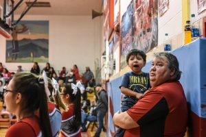 Tracy Lawrence (R), 51, a furloughed Bureau of Indian Affairs worker, holds his grandson while attending a high school basketball game on the Cheyenne River Reservation in Eagle Butte, South Dakota, U.S. January 26, 2019. REUTERS/Stephanie Keith
