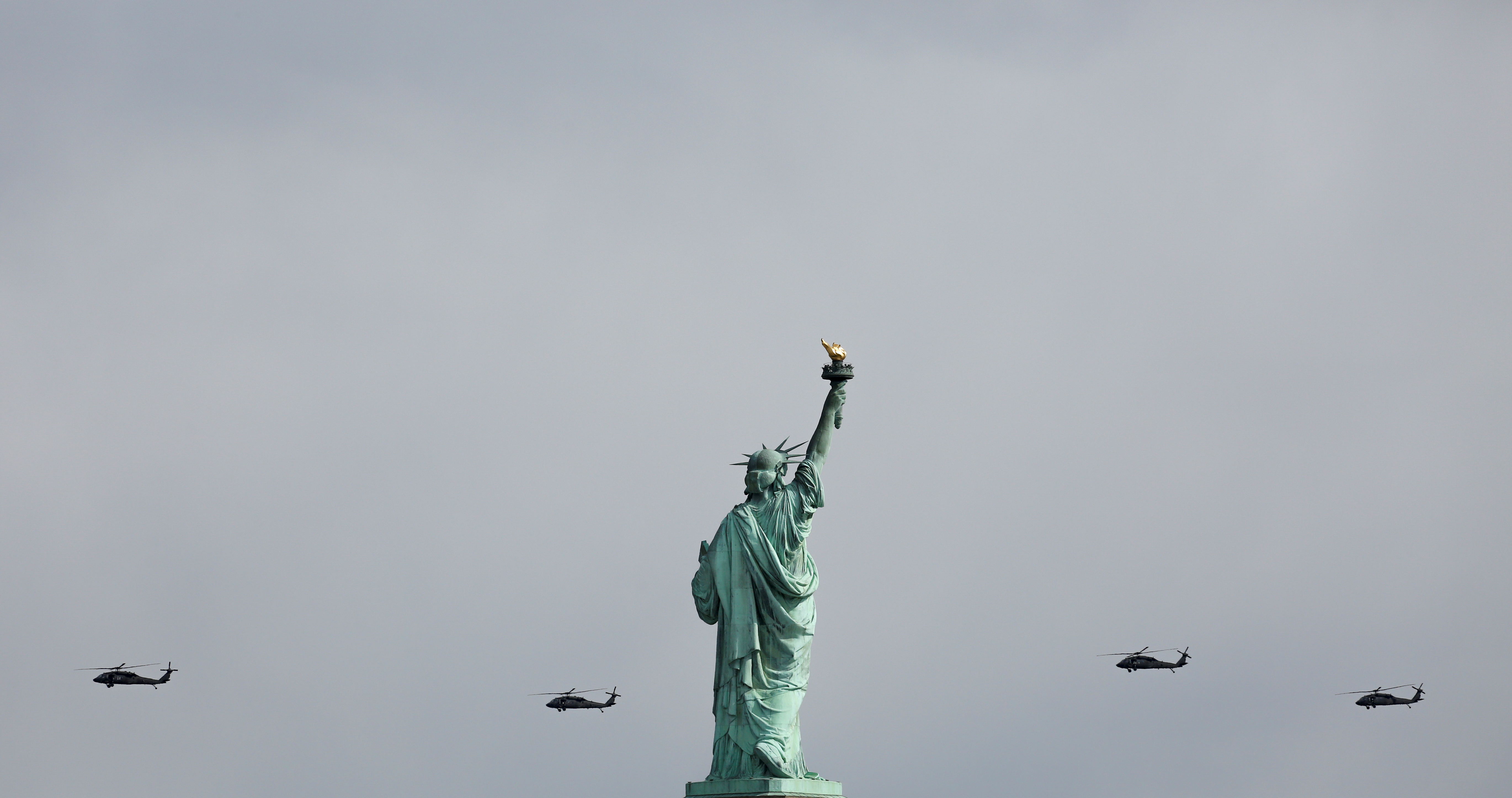 Military helicopters, conducting a military training exercise, fly past the Statue of Liberty in this photograph taken from Liberty State Park in Jersey City, New Jersey, U.S., March 11, 2017. REUTERS/Ashlee Espinal
