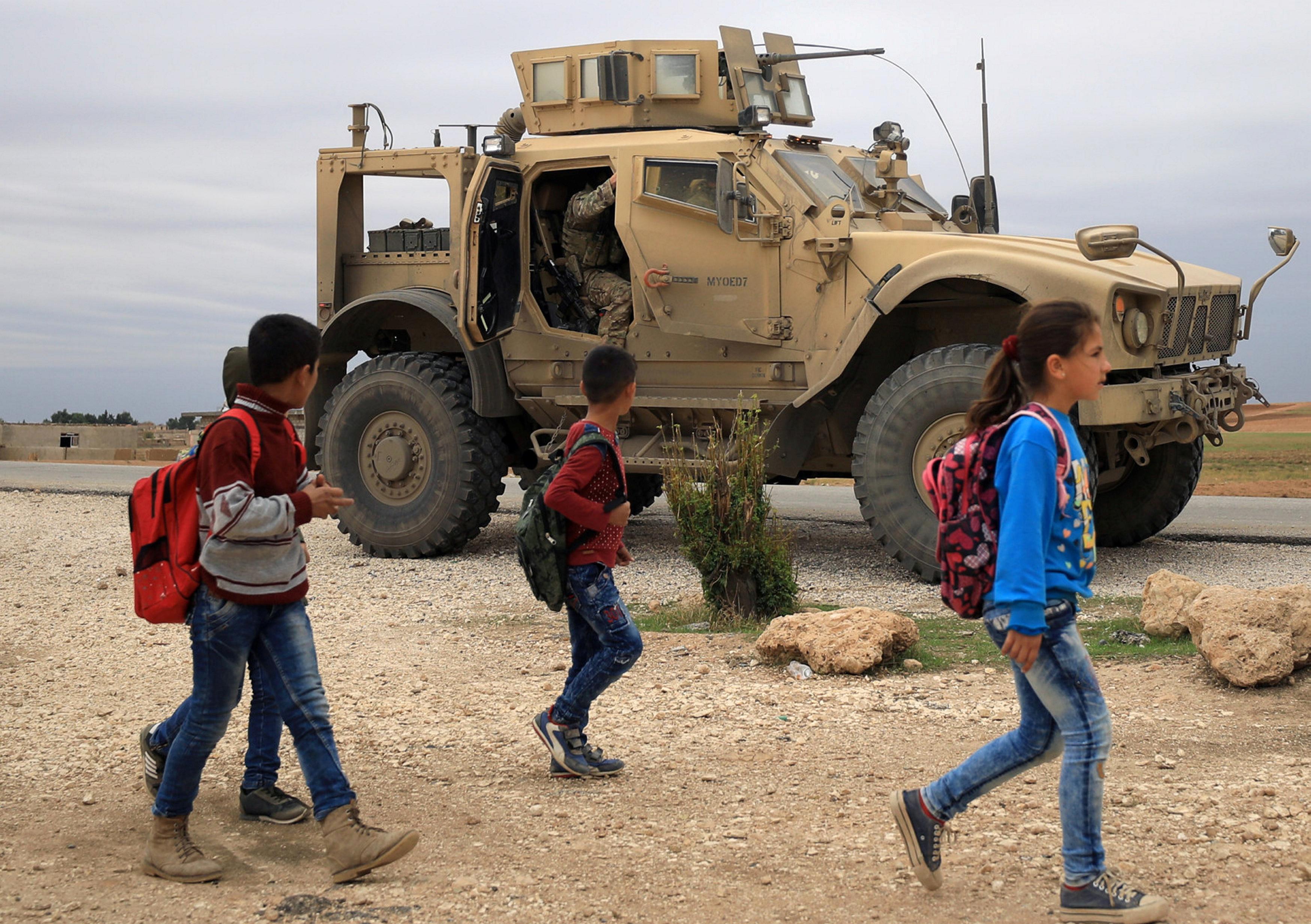 FILE PHOTO: Syrian schoolchildren walk as U.S. troops patrol near Turkish border in Hasakah, Syria Nov. 4, 2018. REUTERS/Rodi Said/File Photo