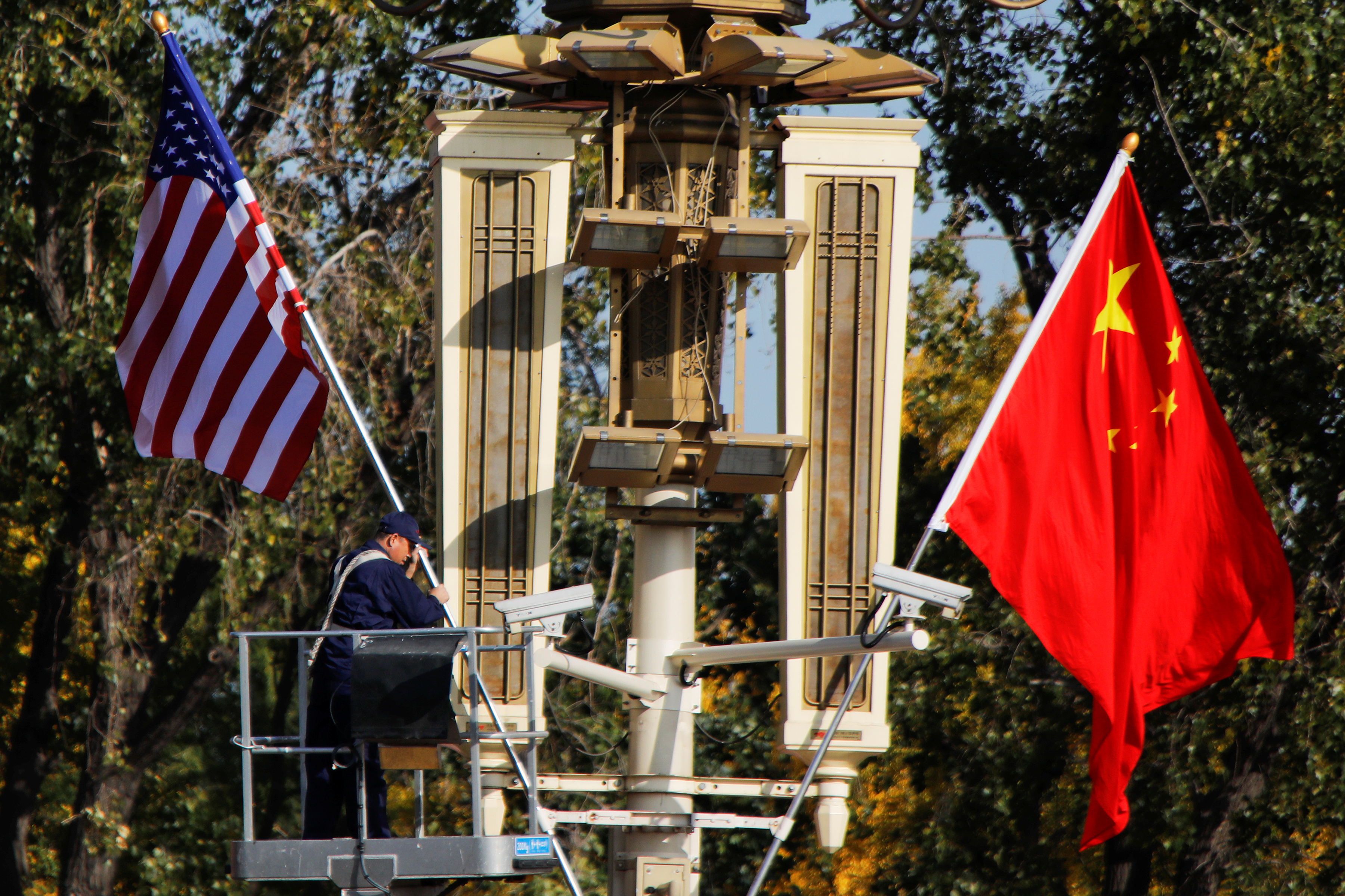 FILE PHOTO - A worker places U.S. and China flags near the Forbidden City ahead of a visit by U.S. President Donald Trump to Beijing, in Beijing, China November 8, 2017. REUTERS/Damir Sagolj