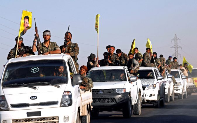 FILE PHOTO: Fighters of Syrian Democratic Forces ride on trucks as their convoy passes in Ain Issa, Syria October 16, 2017. REUTERS/Erik De Castro/File Photo