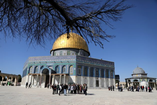 Tourists take part in the Dual Narrative tour lead by tour guides, Noor Awad, a Palestinian from Bethlehem, and Lana Zilberman Soloway, a Jewish seminary student, stand next to the Dome of the Rock on the compound known to Jews as Temple Mount and to Muslims as The Noble Sanctuary, in Jerusalem's Old City, February 4, 2019. Picture taken February 4, 2019. REUTERS/Ammar Awad