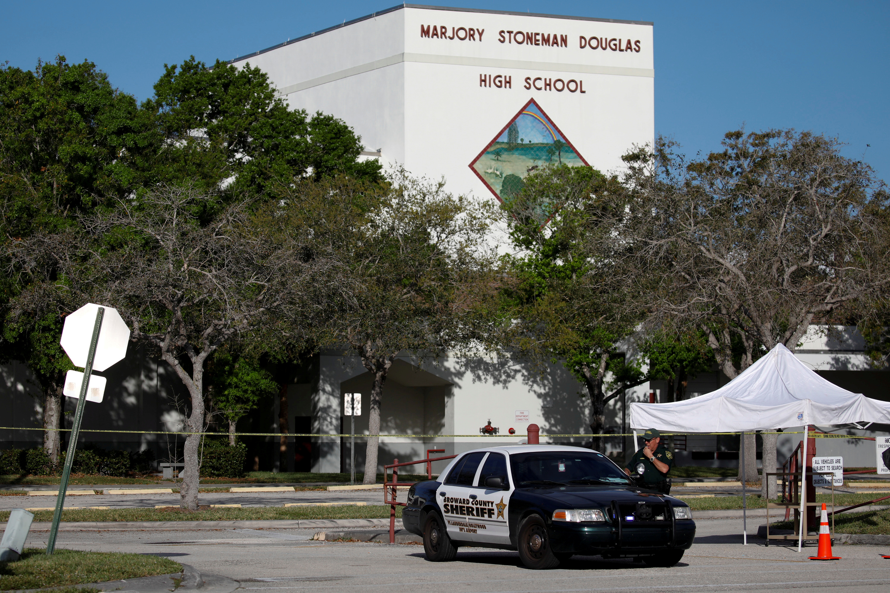 FILE PHOTO: A police officer Jamie Rubenstein stands guard in front of the Marjory Stoneman Douglas High School, after the police security perimeter was removed, following a mass shooting in Parkland, Florida, U.S., February 18, 2018. REUTERS/Carlos Garcia Rawlins/File Photo