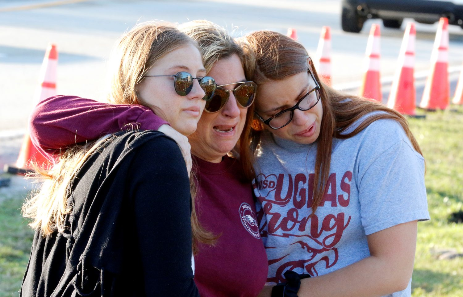 Cheryl Rothenberg embraces her daughters Emma and Sophia as they view a memorial on the one year anniversary of the shooting which claimed 17 lives at Marjory Stoneman Douglas High School in Parkland, Florida, U.S., February 14, 2019. Sophia is a student at the school and Emma is a recent graduate. REUTERS/Joe Skipper