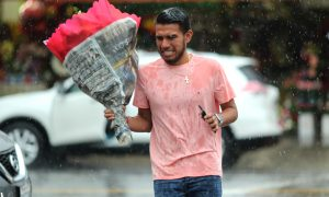 A man carries flowers in the rain in the flower district on Valentine's Day in Los Angeles, California, U.S., February 14, 2019. REUTERS/Lucy Nicholson