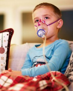 "FILE PHOTO: Weston Tuttle, 5, does a nebulizer treatment while watching ""Frosty the Snowman"" at their home in Steilacoom, Washington, U.S. November 28, 2018. REUTERS/Lindsey Wasson/File Photo"