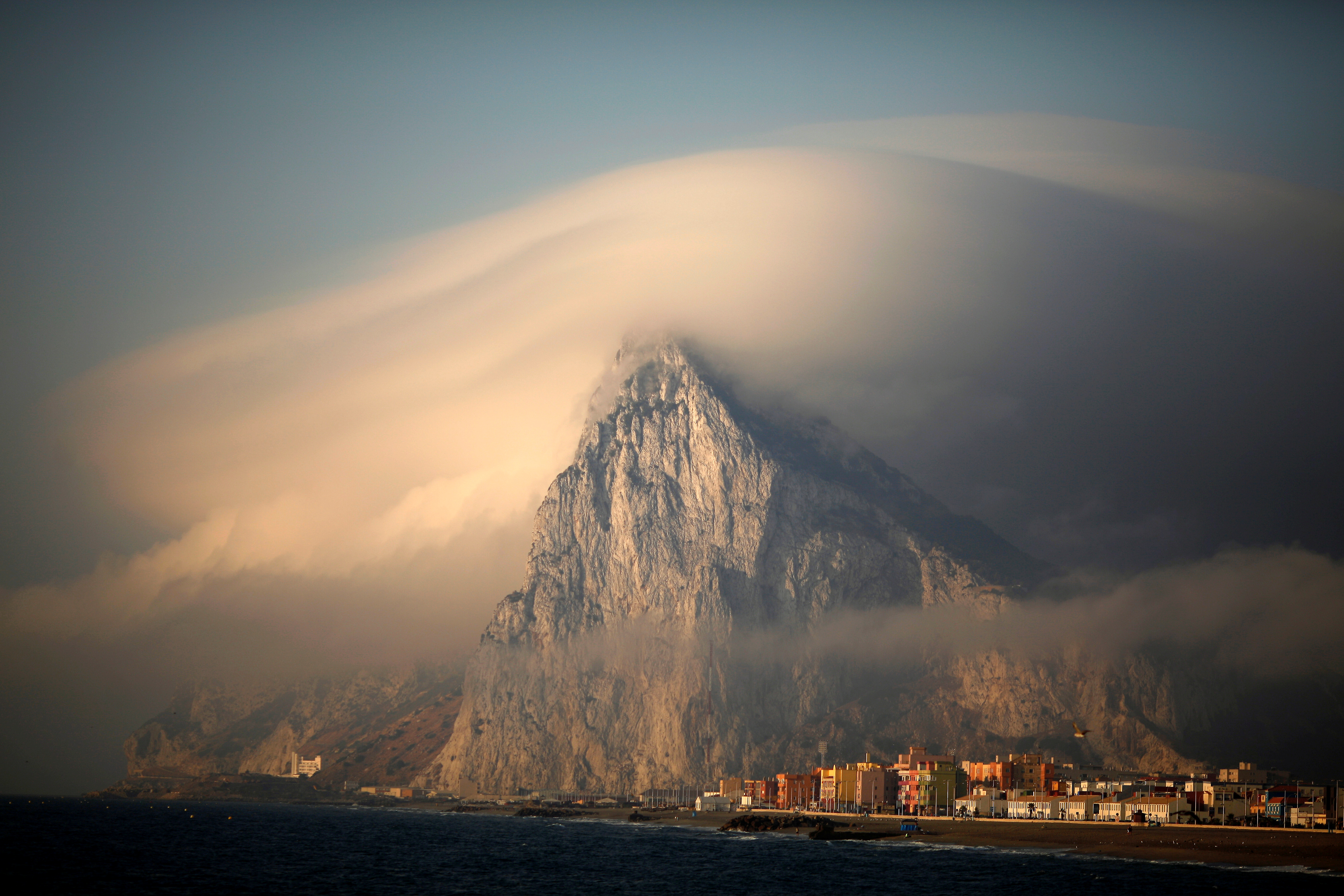 FILE PHOTO: A cloud partially covers the tip of the Rock of the British territory of Gibraltar at sunrise from La Atunara port before Spanish fishermen sail in their fishing boats with their relatives to take part in a protest at an area of the sea where an artificial reef was built by Gibraltar using concrete blocks, in Algeciras bay, La Linea de la Concepcion in southern Spain August 18, 2013. REUTERS/Jon Nazca