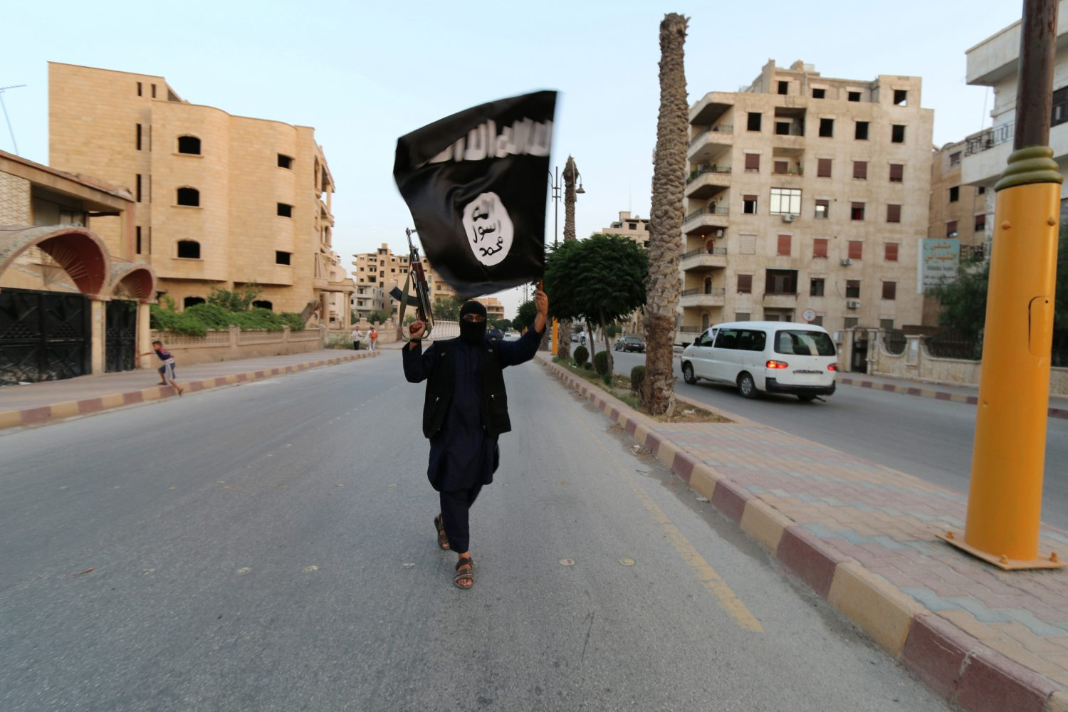 FILE PHOTO - A member loyal to the Islamic State in Iraq and the Levant (ISIL) waves an ISIL flag in Raqqa, Syria June 29, 2014. REUTERS/Stringer/File Photo