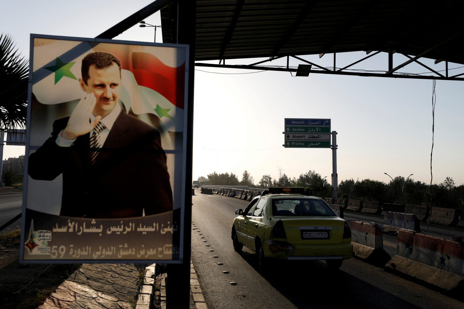 FILE PHOTO: A poster of Syrian President Bashar al-Assad is seen on the main road to the airport in Damascus, Syria April 14, 2018. REUTERS/Omar Sanadiki/File Photo