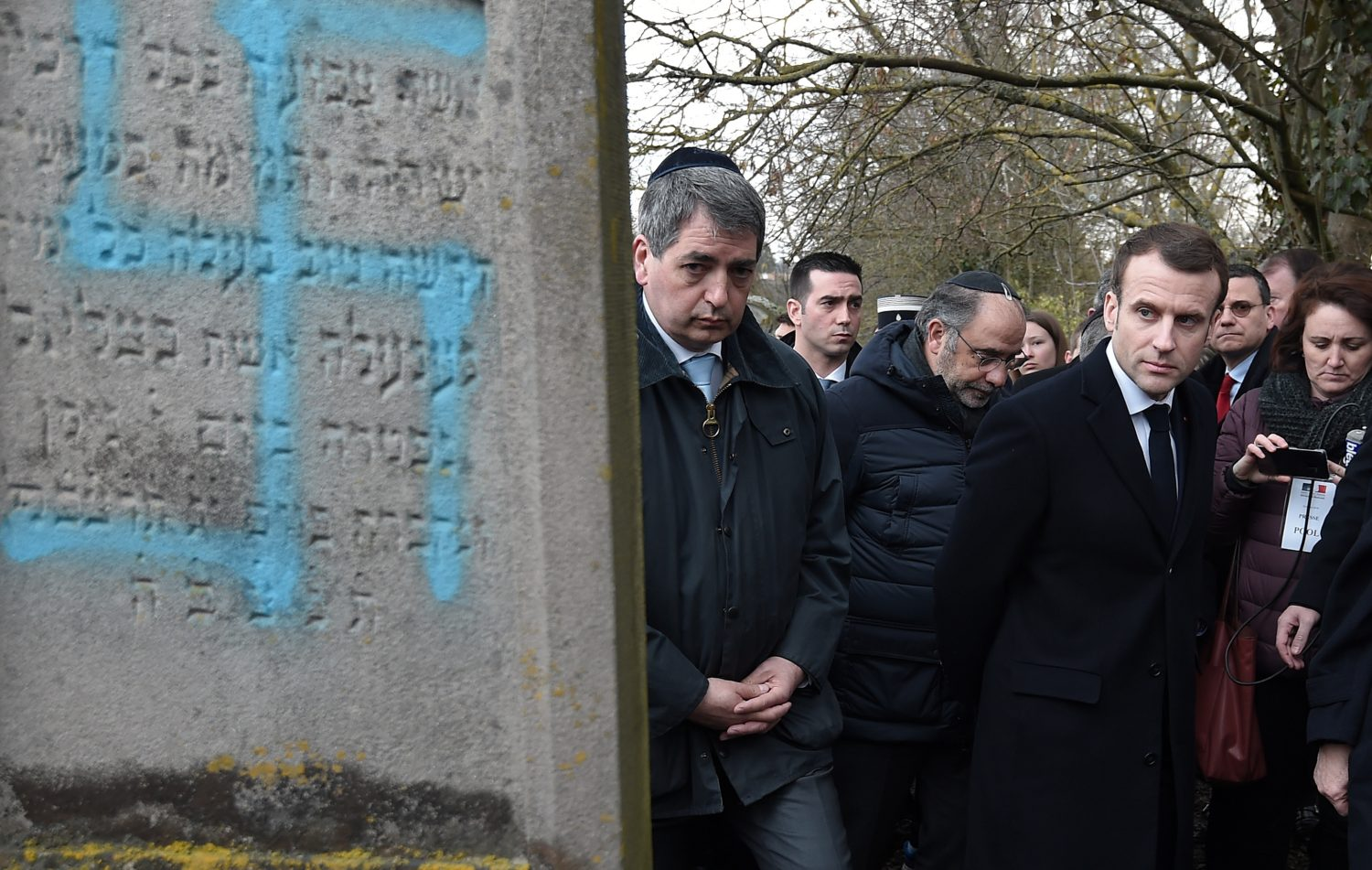 French President Emmanuel Macron looks at a grave vandalised with a swastika during a visit at the Jewish cemetery in Quatzenheim, France February 19, 2019. Frederick Florin/Pool via REUTERS