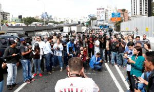 Members of the media wait for Juan Guaido, who many nations have recognized as the country's rightful interim ruler, to pass by on the motorway, in Caracas, Venezuela February 21, 2019. REUTERS/Carlos Jasso