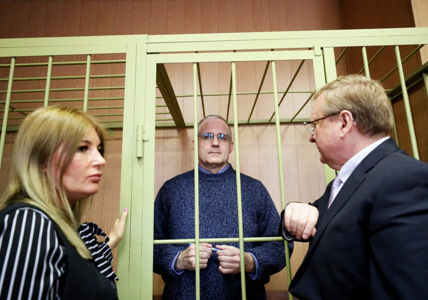 Former U.S. marine Paul Whelan who is being held on suspicion of spying talks with his lawyers Vladimir Zherebenkov and Olga Kralova, as he stands in the courtroom cage after a ruling regarding extension of his detention, in Moscow, Russia, February 22, 2019. REUTERS/Shamil Zhumatov