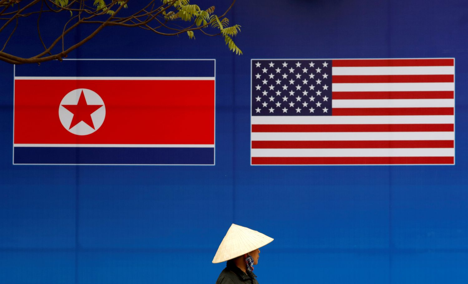 A person walks past a banner showing North Korean and U.S. flags ahead of the North Korea-U.S. summit in Hanoi, Vietnam, February 25, 2019. REUTERS/Kim Kyung-Hoon