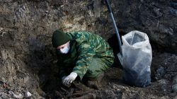 """A soldier from a special """"search battalion"""" of Belarus Defence Ministry takes part in the exhumation of a mass grave containing the remains of about 730 prisoners of a former Jewish ghetto, discovered at a construction site in the centre of Brest, Belarus February 26, 2019. REUTERS/Vasily Fedosenko"""