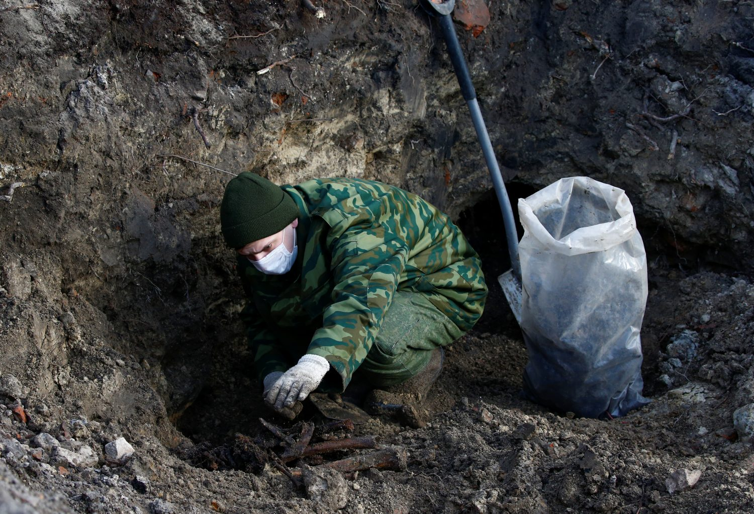 "A soldier from a special ""search battalion"" of Belarus Defence Ministry takes part in the exhumation of a mass grave containing the remains of about 730 prisoners of a former Jewish ghetto, discovered at a construction site in the centre of Brest, Belarus February 26, 2019. REUTERS/Vasily Fedosenko"