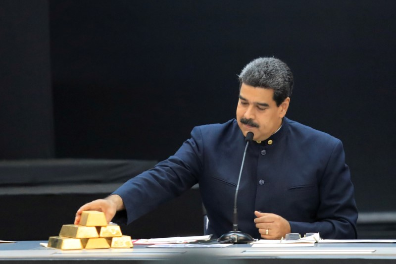 FILE PHOTO: Venezuela's President Nicolas Maduro touches a gold bar as he speaks during a meeting with the ministers responsible for the economic sector at Miraflores Palace in Caracas, Venezuela March 22, 2018. REUTERS/Marco Bello/File Photo