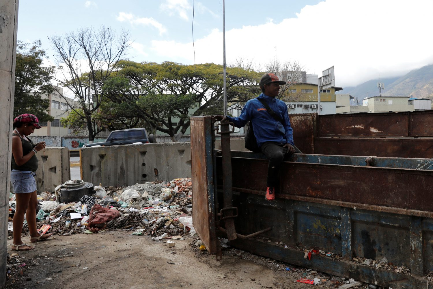 A man sits on a rubbish container in Caracas, Venezuela February 26, 2019. Picture taken February 26, 2019. REUTERS/Carlos Jasso