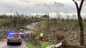 People clear fallen trees and debris on a road following a tornado in Beauregard, Alabama, U.S. in this March 3, 2019 still image obtained from social media video. SCOTT FILLMER /via REUTERS
