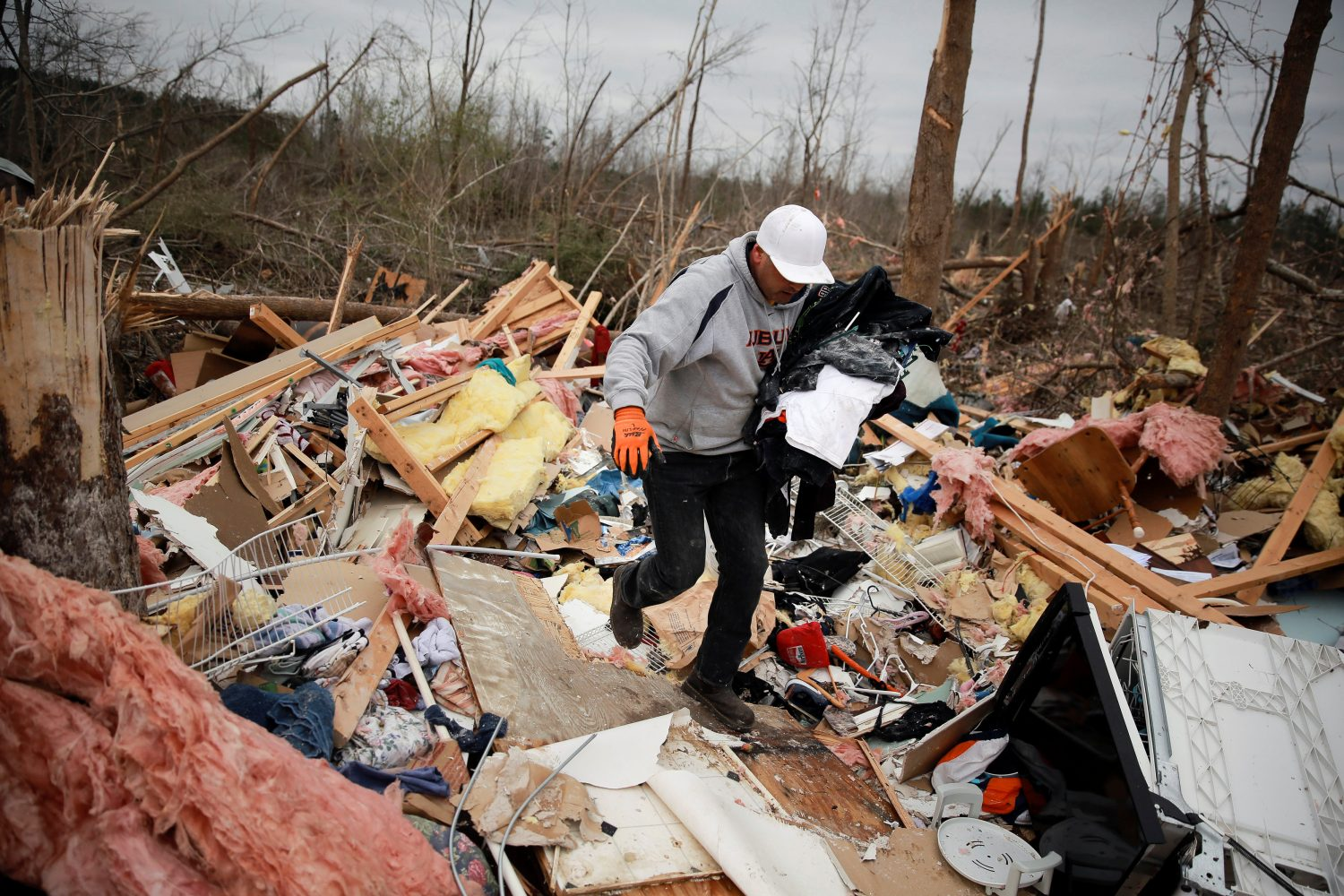 Dax Leandro salvages clothing from the wreckage of his friend's home after two back-to-back tornadoes touched down, in Beauregard, Alabama, U.S., March 4, 2019. REUTERS/Elijah Nouvelage