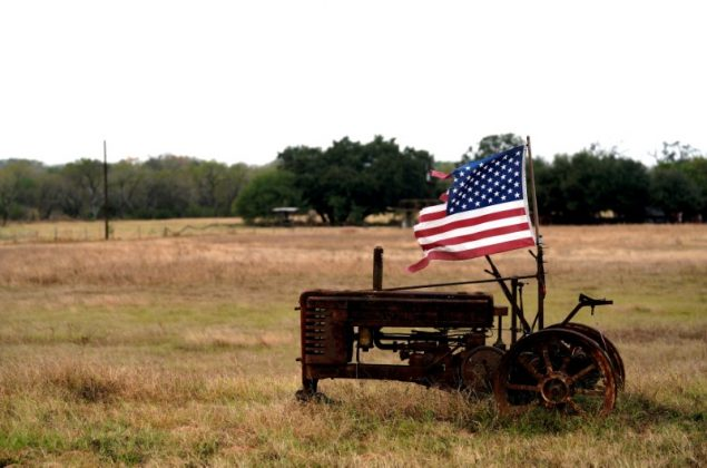 FILE PHOTO: A tattered U.S. flag flies on an old tractor in a farm field outside Sutherland Springs,Texas, U.S. November 8, 2017. REUTERS/Rick Wilking