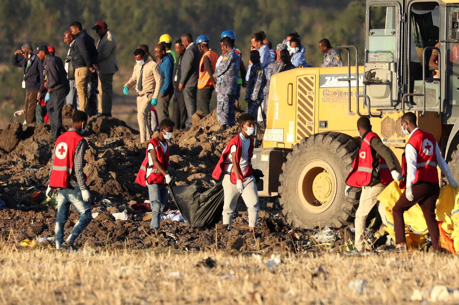 Members of the search and rescue mission carry dead bodies at the scene of the Ethiopian Airlines Flight ET 302 plane crash, near the town of Bishoftu, southeast of Addis Ababa, Ethiopia March 10, 2019. REUTERS/Tiksa Negeri