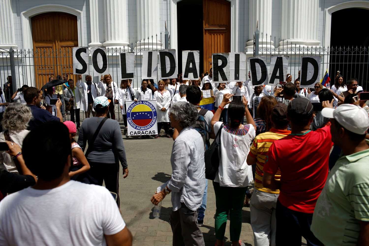 "Venezuelans, including doctors, hold banners that read ""Solidarity"" as they gather outside a church after a mass during an ongoing blackout in downtown Caracas, Venezuela March 10, 2019. REUTERS/Marco Bello"