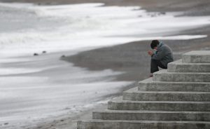 A woman faces the sea to pray while mourning the victims of the March 11, 2011 earthquake and tsunami disaster, in Iwaki, Fukushima prefecture, Japan March 11, 2019. Mandatory credit Kyodo/via REUTERS