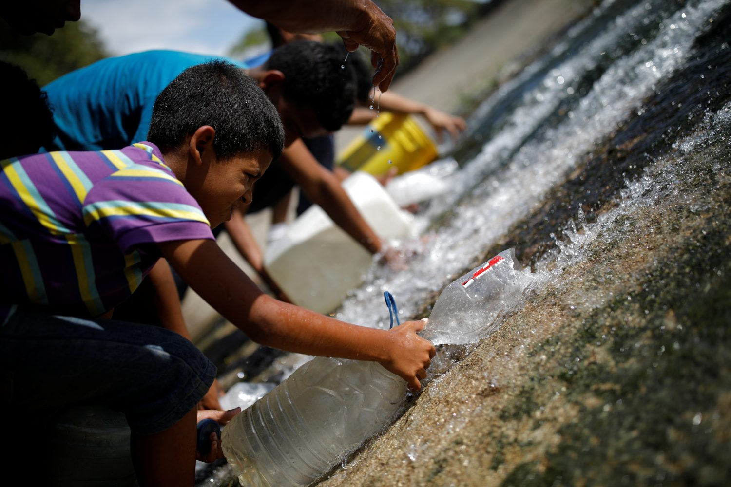 People collect water released through a sewage drain that feeds into the Guaire River, which carries most of the city's wastewater, in Caracas, Venezuela March 11, 2019. REUTERS/Carlos Garcia Rawlins