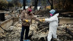FILE PHOTO: Vanthy Bizzle hands some small religious figurines to her husband Brett Bizzle in the remains of their home after returning for the first time since the Camp Fire forced them to evacuate in Paradise, California, U.S. November 22, 2018. REUTERS/Elijah Nouvelage/File Photo