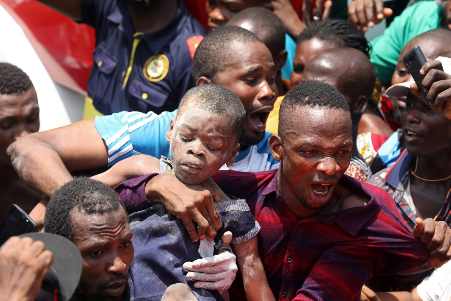 Men carry a boy who was rescued at the site of a collapsed building containing a school in Nigeria's commercial capital of Lagos, Nigeria March 13, 2019. REUTERS/Temilade Adelaja