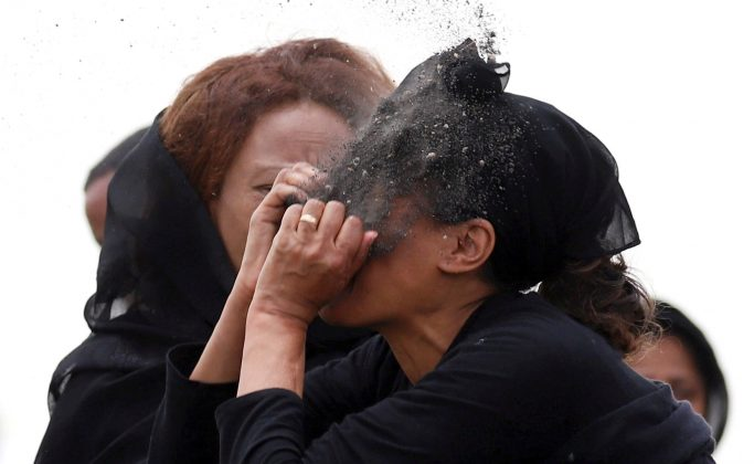 A relative puts soil on her face as she mourns at the scene of the Ethiopian Airlines Flight ET 302 plane crash, near the town Bishoftu, near Addis Ababa, Ethiopia March 14, 2019. REUTERS/Tiksa Negeri
