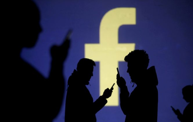 FILE PHOTO: Silhouettes of mobile users are seen next to a screen projection of Facebook logo in this picture illustration taken March 28, 2018. REUTERS/Dado Ruvic