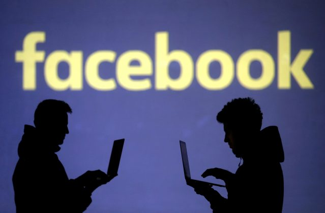 FILE PHOTO: Silhouettes of laptop users are seen next to a screen projection of Facebook logo in this picture illustration taken March 28, 2018. REUTERS/Dado Ruvic/Illustration/File Photo