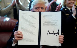 U.S. President Donald Trump holds up his veto of the congressional resolution to end his emergency declaration to get funds to build a border wall after signing it in the Oval Office of the White House in Washington, U.S., March 15, 2019. REUTERS/Jonathan Ernst