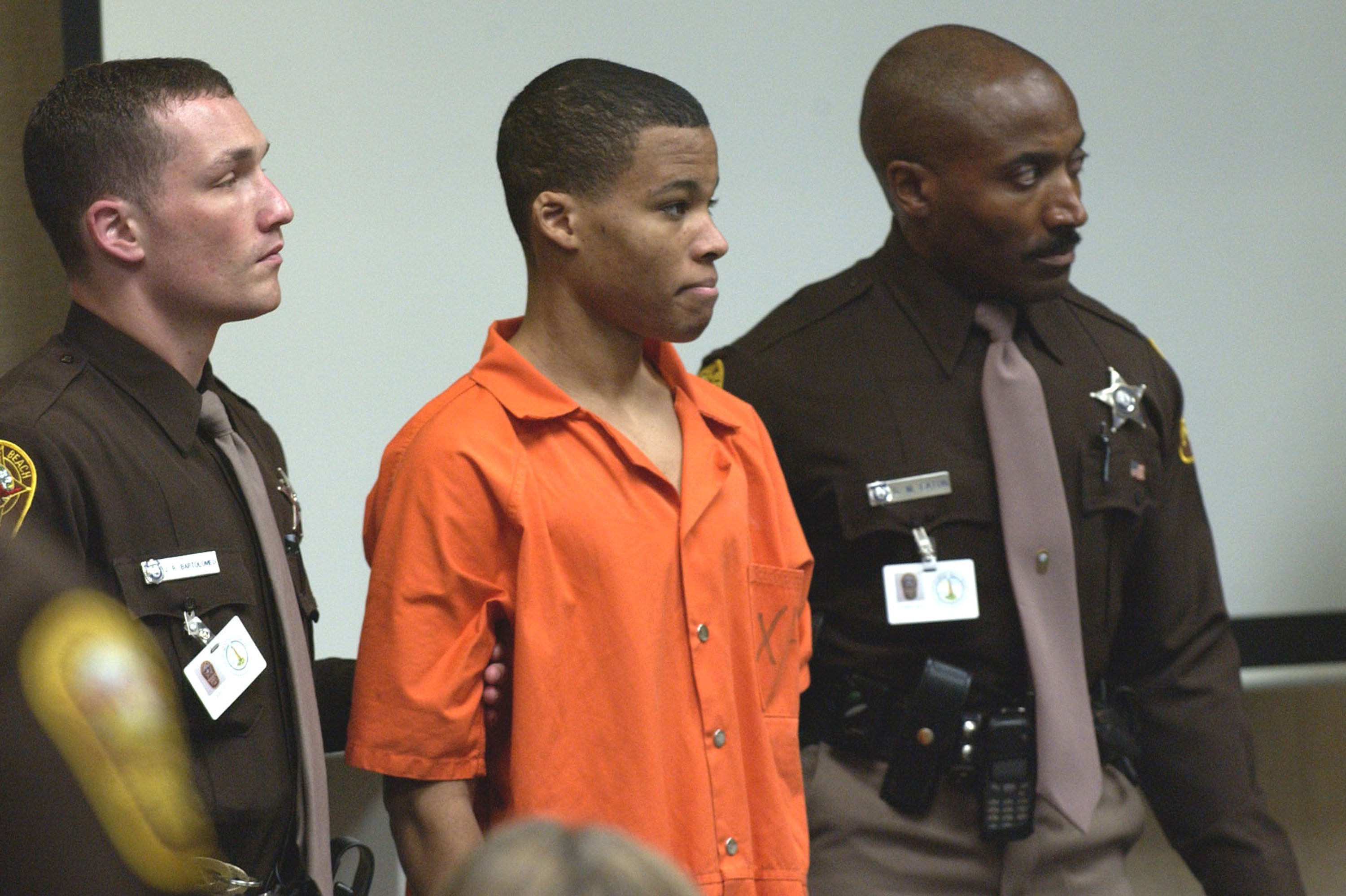 FILE PHOTO : 18-year old sniper suspect Lee Boyd Malvo is surrounded by deputies as he is brought into court to be identified by a witness during the trial of sniper suspect John Allen Muhammad at the Virginia Beach Circuit Court in Virginia Beach, Virginia, U.S., October 22, 2003. REUTERSDavis Turner/POOL/File Photo