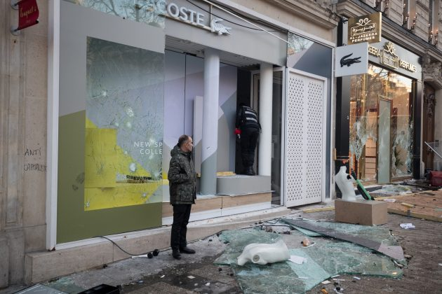 "A man stand in front of a damaged shop on the Champs Elysees avenue during a demonstration by the ""yellow vests"" movement in Paris, France, March 16, 2019. Picture taken March 16, 2019. REUTERS/Philippe Wojazer"