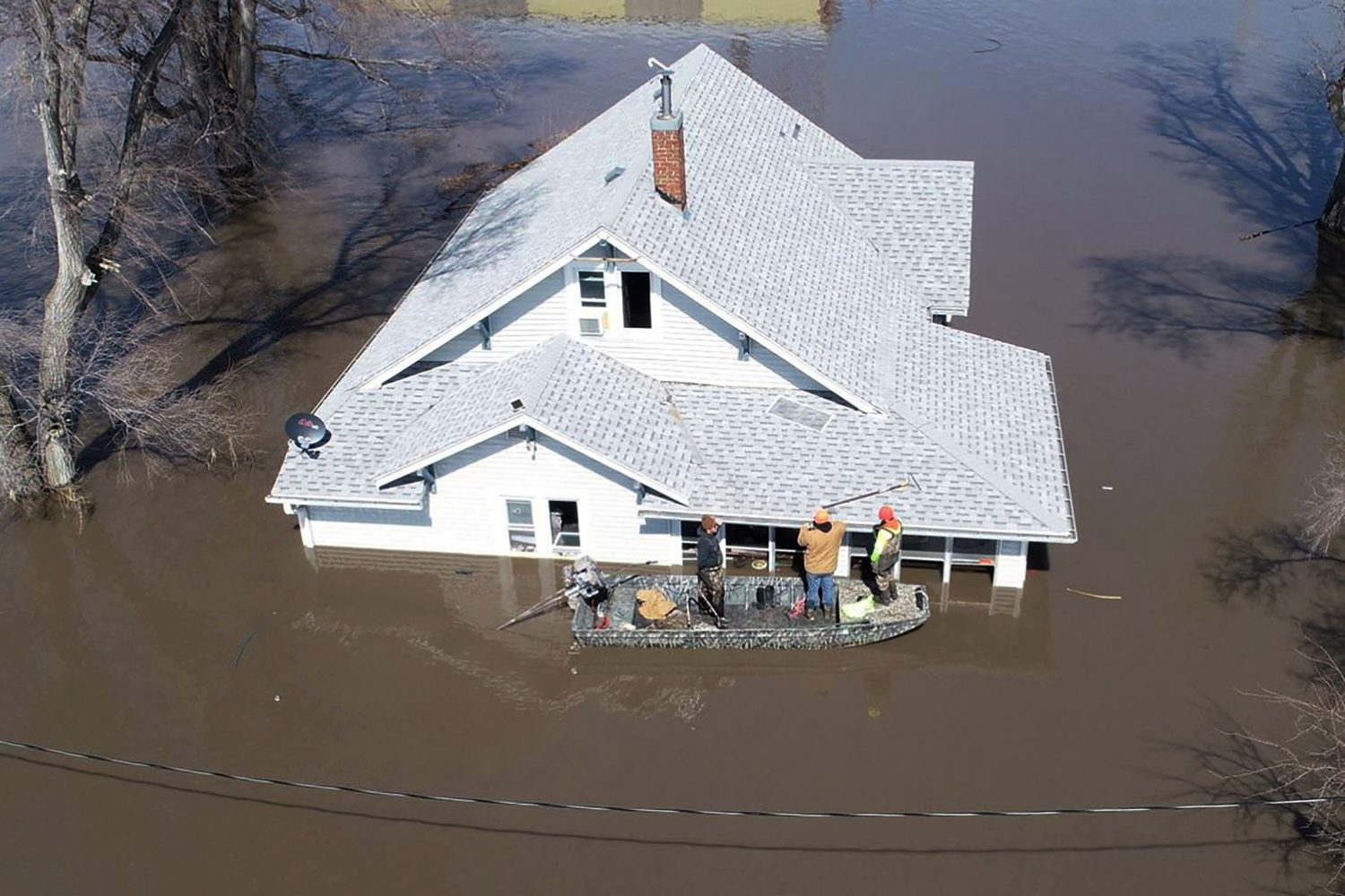 Lanni Bailey and a team from Muddy Paws Second Chance Rescue enter a flooded house to pull out several cats during the flooding of the Missouri River near Glenwood, Iowa, U.S. March 18, 2019. Passport Aerial Photography/Handout via REUTERS