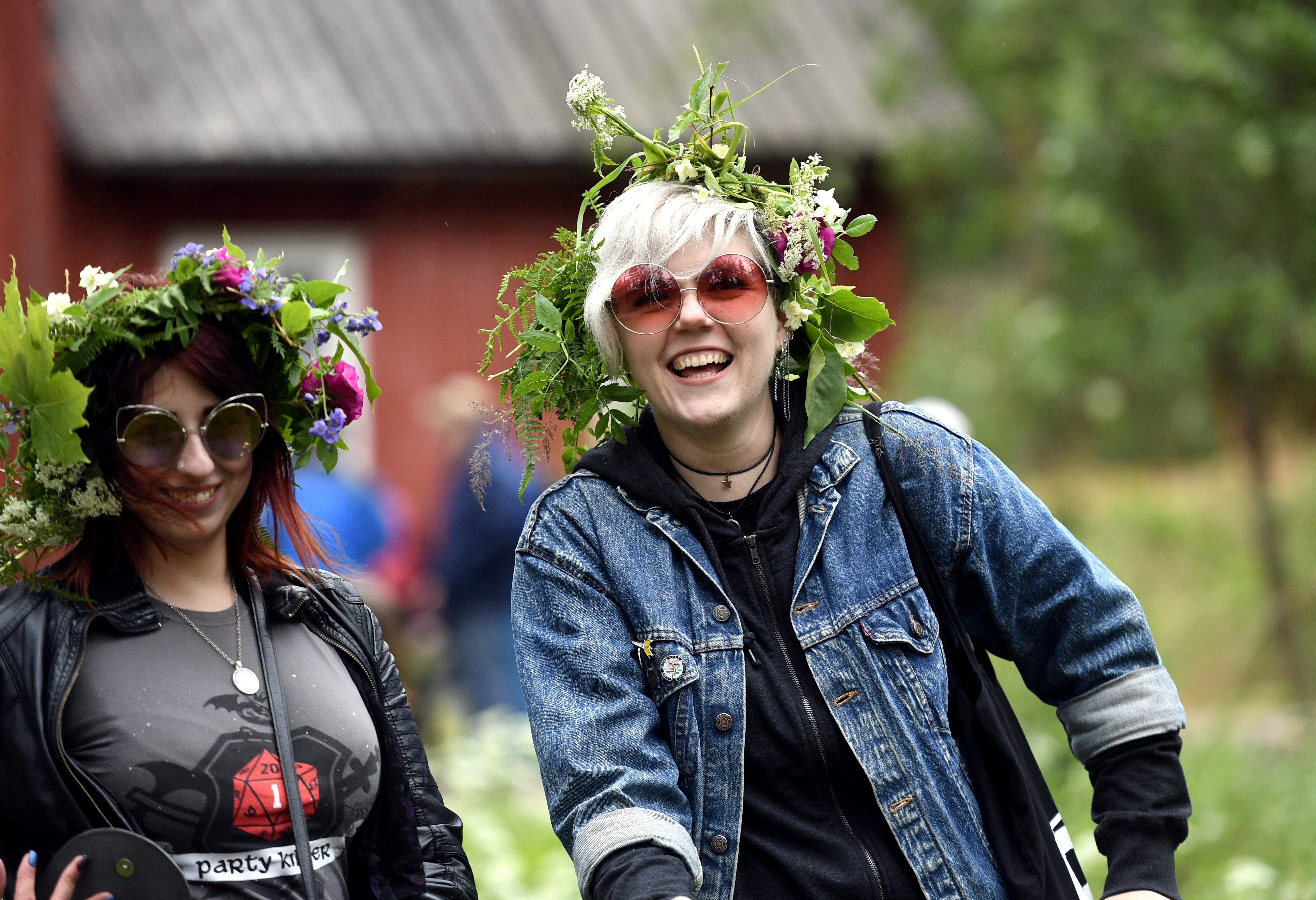 FILE PHOTO: Girls wearing flower garlands celebrate the summer solstice during the Seurasaari open-air museum's Midsummer Eve festival in Helsinki, Finland June 22, 2018. LEHTIKUVA / Heikki Saukkomaa via REUTERS/File Photo