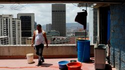 Wilson Hernandez stands next to buckets of water on the roof of an apartment block in Caracas, Venezuela, March 17, 2019. REUTERS/Carlos Jasso