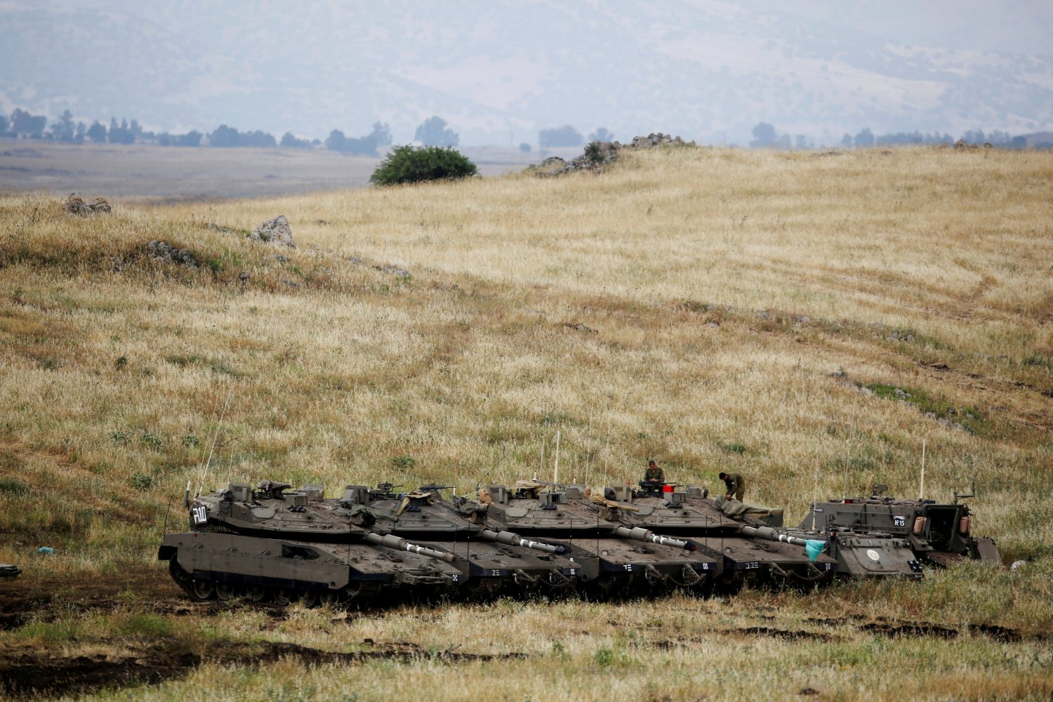 FILE PHOTO: Israeli soldiers stand on tanks near the Israeli side of the border with Syria in the Israeli-occupied Golan Heights, Israel May 9, 2018. REUTERS/Amir Cohen/File Photo