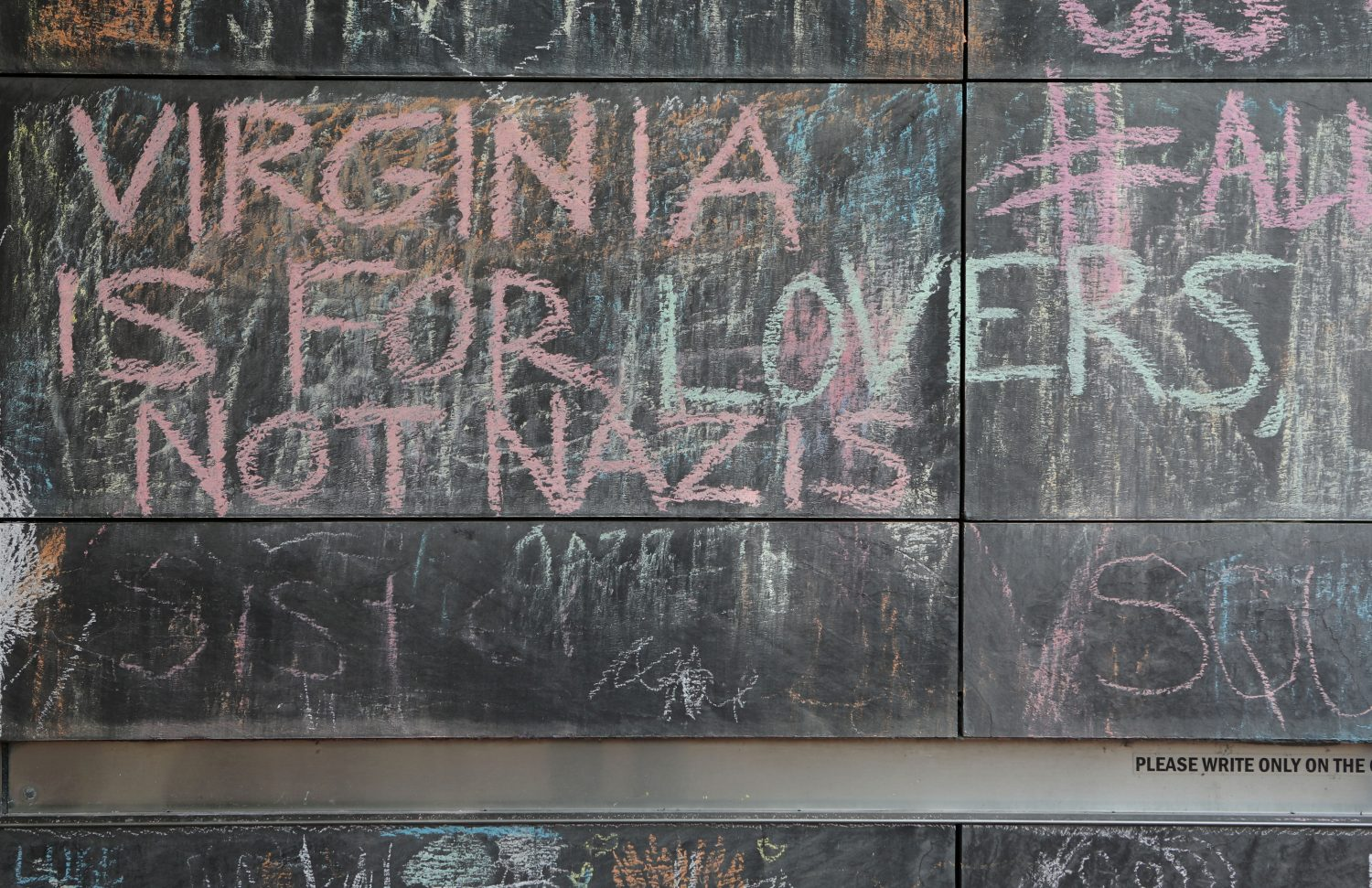 "FILE PHOTO: Messages are left on a chalkboard wall ahead of the one-year anniversary of 2017 Charlottesville ""Unite the Right"" protests, in Charlottesville, Virginia, U.S., August 10, 2018. REUTERS/Jim Urquhart/File Photo"