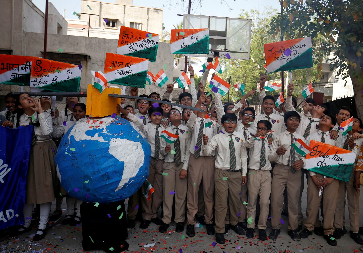 Students cheer as they raise flags to celebrate after India shot down one of its satellites in space with an anti-satellite missile in a test, inside their school premises in Ahmedabad, India, March 27, 2019. REUTERS/Amit Dave