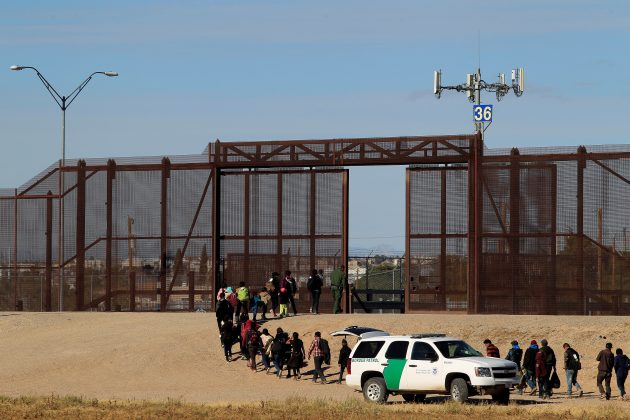 FILE PHOTO: Migrants from Central America are seen escorted by U.S. Customs and Border Protection (CBP) officials after crossing the border from Mexico to surrender to the officials in El Paso, Texas, U.S., in this pictured taken from Ciudad Juarez, Mexico December 3, 2018. REUTERS/Jose Luis Gonzalez/File Photo