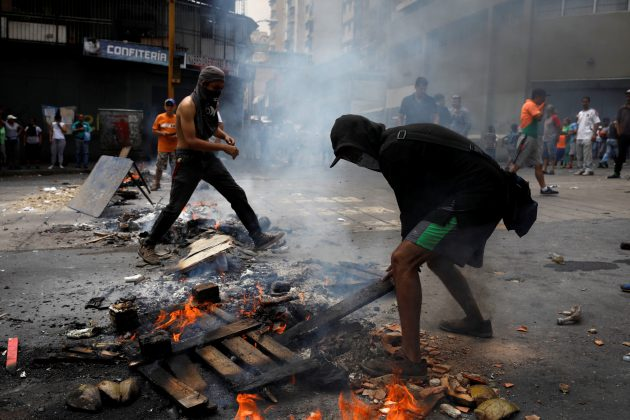 Demonstrators set up a fire barricade at a protest against the government of Venezuelan President Nicolas Maduro in Caracas, Venezuela March 31, 2019. REUTERS/Carlos Garcia Rawlins